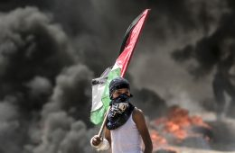 TOPSHOT - A Palestinian boy holding his national flag looks at clashes with Israeli security forces near the border between the Gaza Strip and Israel east of Gaza City on May 14, 2018, as Palestinians protest over the inauguration of the US embassy following its controversial move to Jerusalem. Dozens of Palestinians were killed by Israeli fire on May 14 as tens of thousands protested and clashes erupted along the Gaza border against the US transfer of its embassy to Jerusalem, after months of global outcry, Palestinian anger and exuberant praise from Israelis over President Donald Trump's decision tossing aside decades of precedent. / AFP PHOTO / MAHMUD HAMS